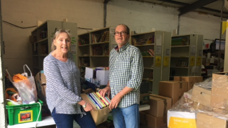 Clare Junak receives book donation from Peter Dobson